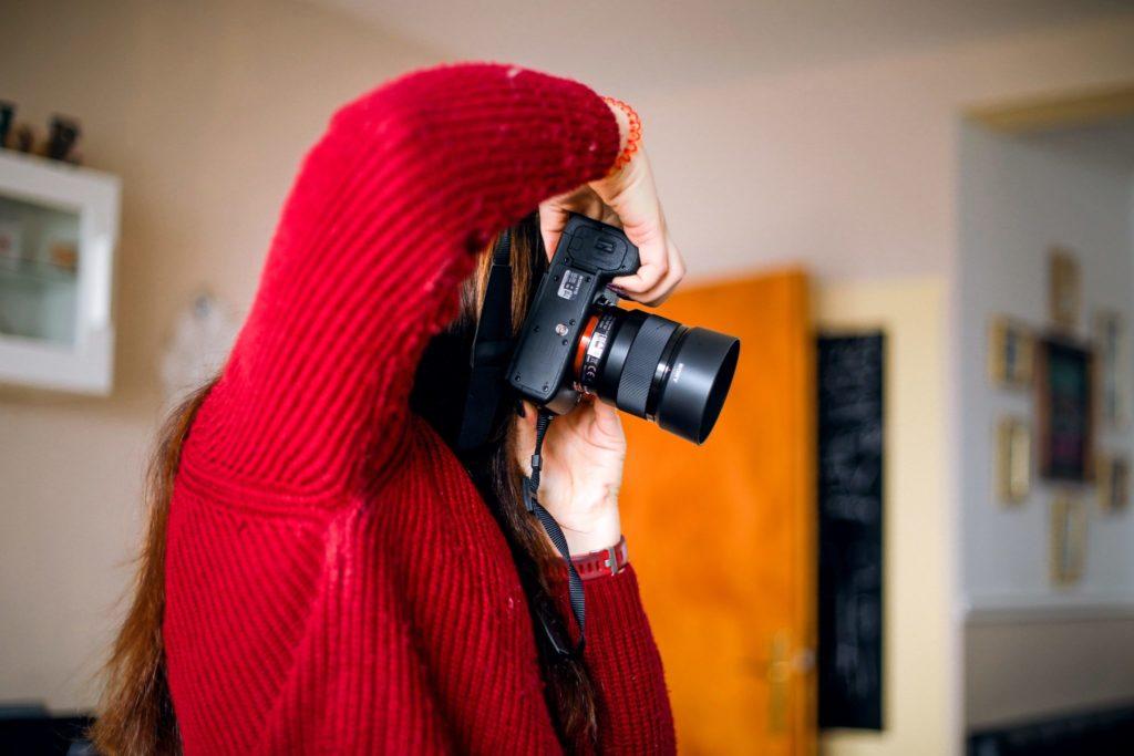 Frau im roten Pullover mit Kamera in der Hand