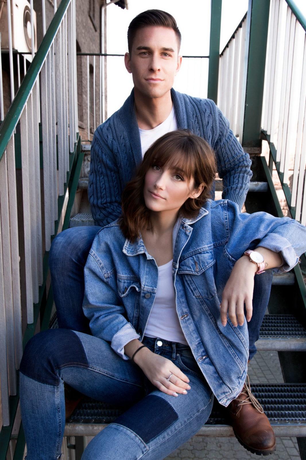 Ein Paar, das auf der Treppe sitzt. Er sitzt einer Stufe höher als sie und sie stützt sich auf seinem Bein ab.