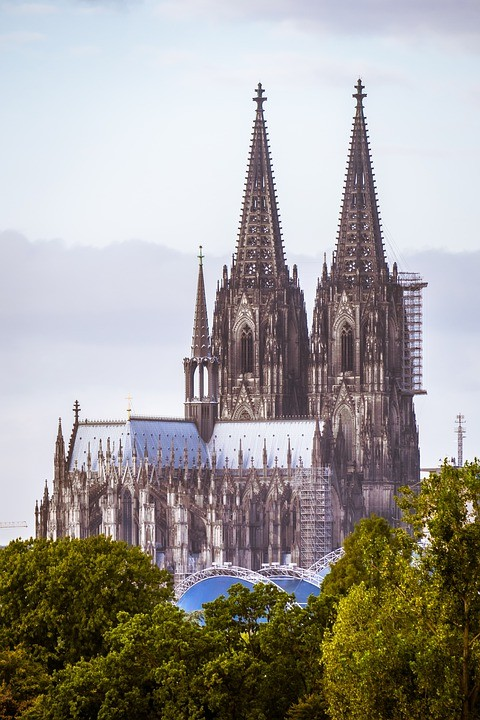 der Kölner Dom mit Bäumen im Hintergrund und blauem Himmel