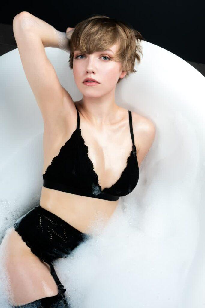 Frau im schwarzen Dessous in einer Badewanne mit Schaum