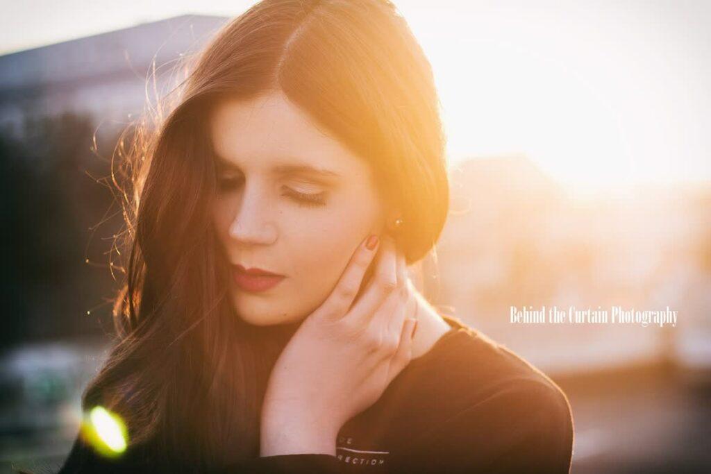 Frau im Abendlicht mit geschlossenen Augen und einer Hand am Gesicht