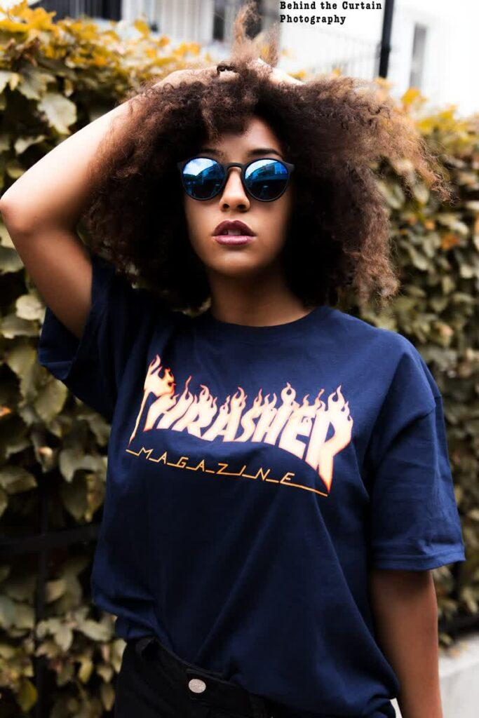 eine schwarze Frau mit lockigen Haare und einer Sonnenbrille auf im T-Shirt vor einer Hecke