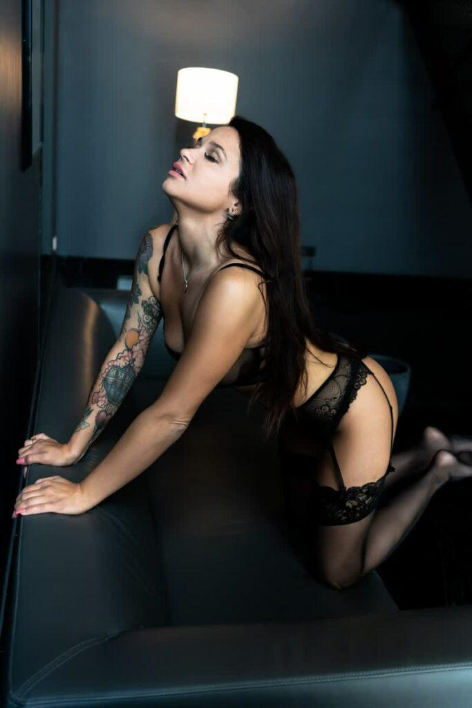 Frau mit Tattoos im Dessous auf einer schwarzen Couch