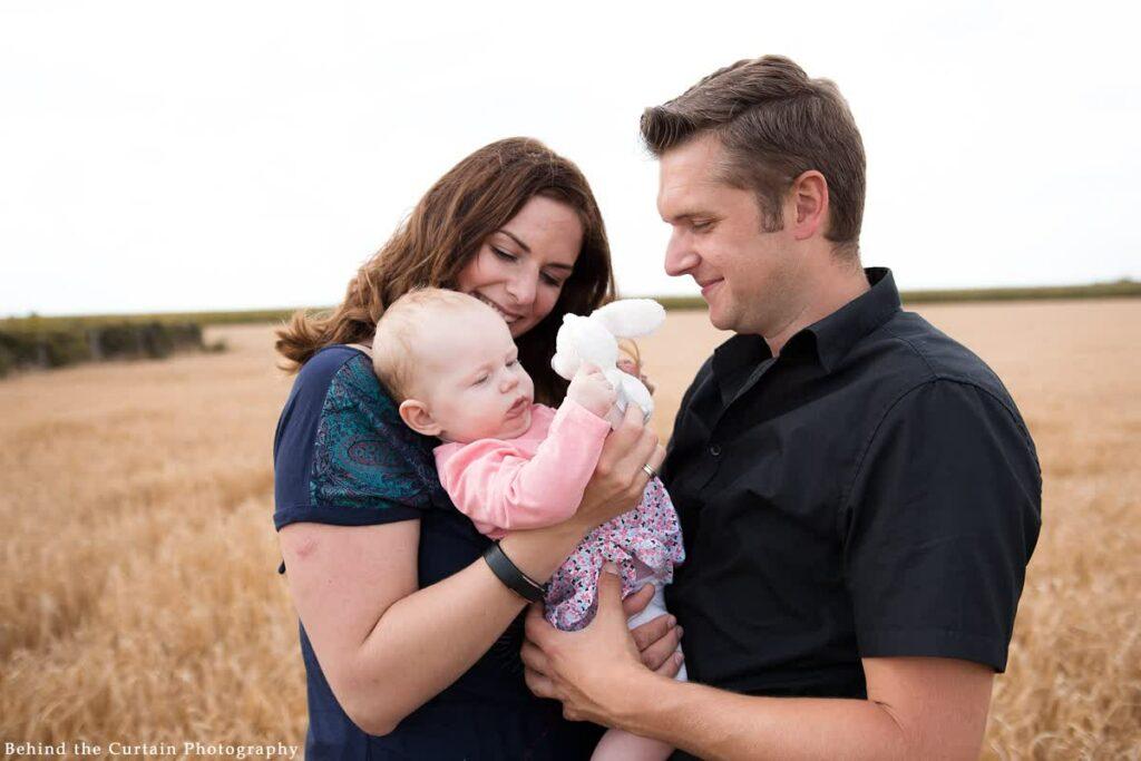 Mutter und Vater halten Kind im Arm und Kind spielt mit Kuscheltier