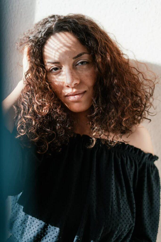 eine Frau mit braunen lockigen Haaren an einem Fenster, der Sonnenschein scheint auf ihr Gesicht