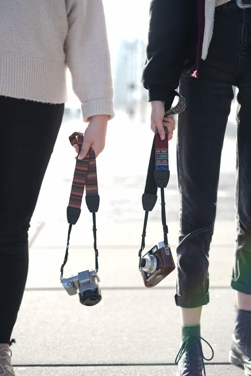 Zwei Mädchen mit kmaeragurt i der Hand mit Gegenlicht fotografiert