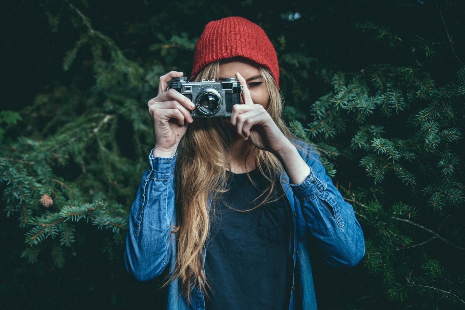 eine Frau mit roter Mütze hinter einer Kamera