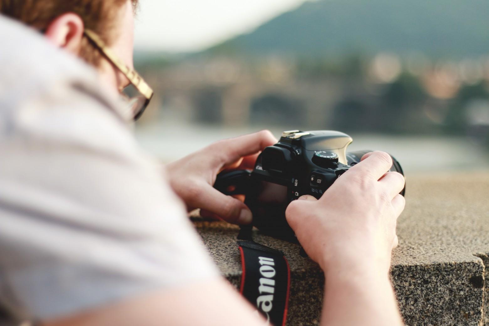 ein mann hinter der Kamera; Kamera auf einer Mauer abgelegt.